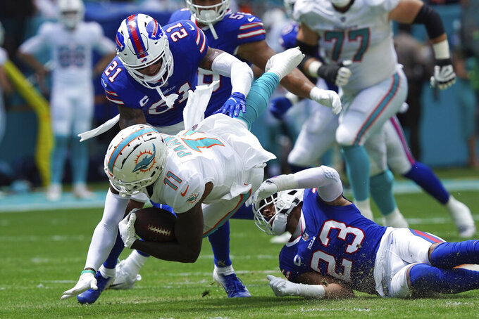 Miami Dolphins wide receiver DeVante Parker (11) is tackled by Buffalo Bills strong safety Micah Hyde (23) and free safety Jordan Poyer (21), during the first half of an NFL football game, Sunday, Sept. 19, 2021, in Miami Gardens, Fla. (AP Photo/Hans Deryk)