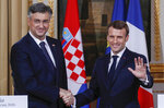French President Emmanuel Macron, right, shakes hands with Croatian Prime Minister Andrej Plenkovic at the Elysee Palace in Paris, Tuesday, Jan. 7, 2020. (Gonzalo Fuentes/Pool via AP)