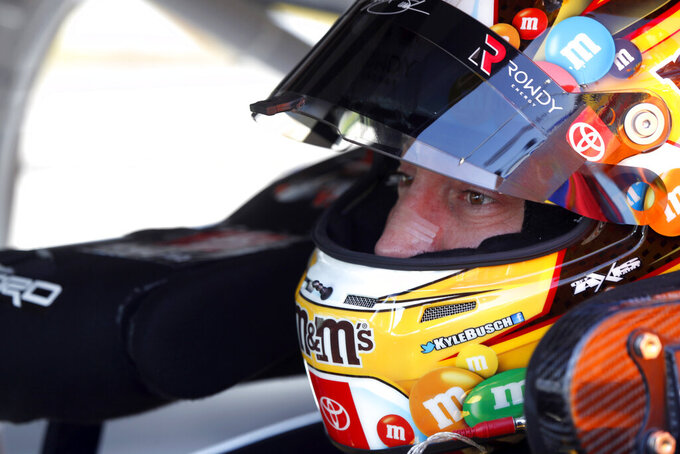 NASCAR Cup Series driver Kyle Busch (18) waits in his car before a NASCAR Cup Series auto race at the Las Vegas Motor Speedway Sunday, Sept. 26, 2021, in Las Vegas. (AP Photo/Steve Marcus)