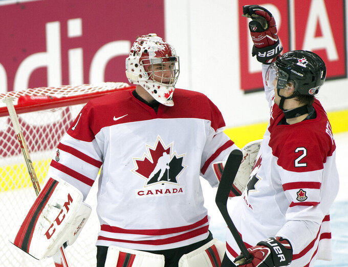 FILE - Team Canada goaltender Jake Paterson is congratulated by defenseman Adam Pelech after defeating Germany in a qualification round game at the IIHF World Junior Hockey Championships in Malmo, Sweden, in this Thursday, Dec. 26, 2013, file photo. Goaltender Jake Paterson is studying to get his real estate license while also playing minor league hockey with the Allen Americans of the ECHL. Paterson joined the Professional Hockey Players Association's career enhancement program last spring after the COVID-19 pandemic hit. (AP Photo/The Canadian Press, Frank Gunn, FIle)