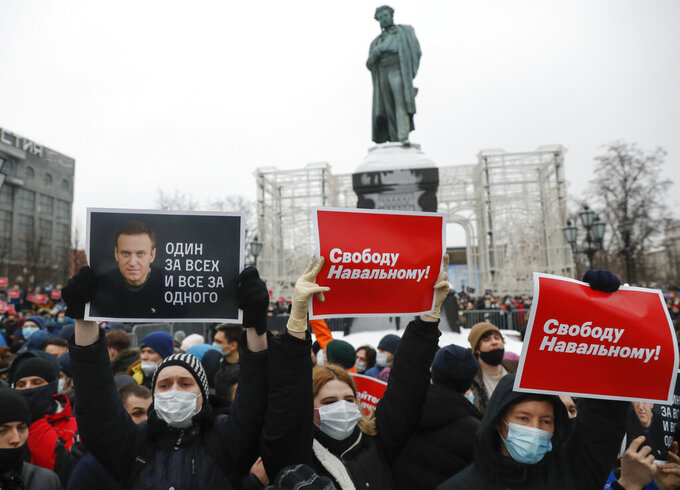 "People gather during a protest against the jailing of opposition leader Alexei Navalny in Pushkin square at the statue of Alexander Pushkin in the background in Moscow, Russia, Saturday, Jan. 23, 2021. Protesters hold posters reading ""Freedom for Navalny!"" and ""One for all and all for one"" with Navalny's portrait. Russian police on Saturday arrested hundreds of protesters who took to the streets in temperatures as low as minus-50 C (minus-58 F) to demand the release of Alexei Navalny, the country's top opposition figure.  Navalny, President Vladimir Putin's most prominent foe, was arrested on Jan. 17 when he returned to Moscow from Germany, where he had spent five months recovering from a severe nerve-agent poisoning that he blames on the Kremlin. (AP Photo/Pavel Golovkin)"
