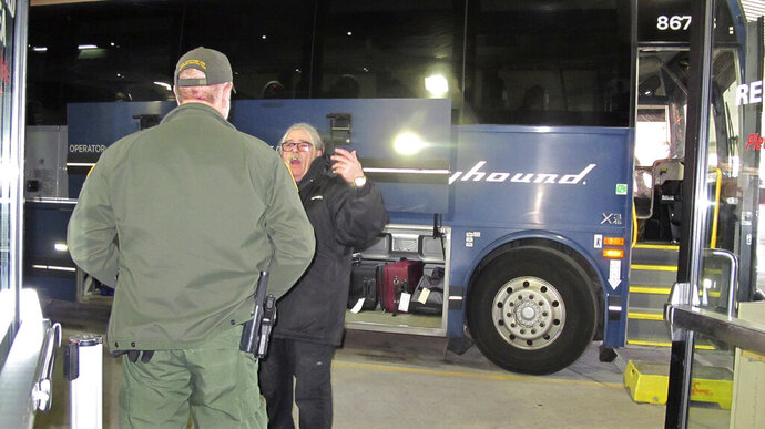 In this Thursday, Feb. 13, 2020 photo, a worker, right, speaks with a Customs and Border Protection agent seeking to board a Greyhound bus headed for Portland, Ore., at the Spokane Intermodal Center, a terminal for buses and Amtrak in Spokane, Wash. A Customs and Border Protection memo obtained by The Associated Press confirms that bus companies such as Greyhound do not have to allow Border Patrol agents on board to conduct routine checks for illegal immigrants, contrary to Greyhound's long insistence that it has no choice but to let the agents on board. (AP Photo/Nicholas K. Geranios)