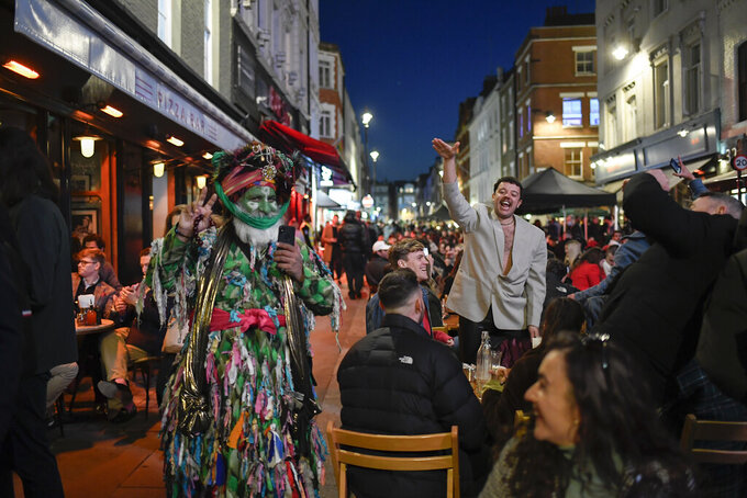 People sit at setup tables outside pubs in Soho, in London, on the day some of England's third coronavirus lockdown restrictions were eased by the British government, Monday, April 12, 2021. Pubs, shops and hairdressers have opened as lockdown restrictions are eased Monday. (AP Photo/Alberto Pezzali)