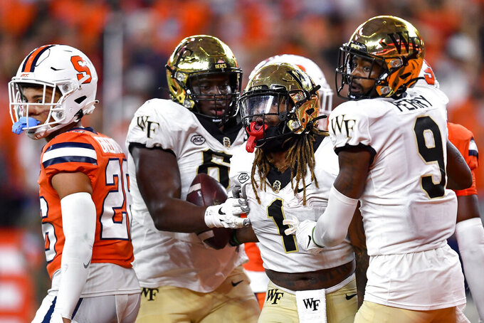 Wake Forest running back Christian Beal-Smith (1) celebrates with offensive lineman DeVonte Gordon (62) and wide receiver A.T. Perry (9) after scoring a touchdown during the second half of an NCAA college football game against Syracuse in Syracuse, N.Y., Saturday, Oct. 9, 2021. (AP Photo/Adrian Kraus)