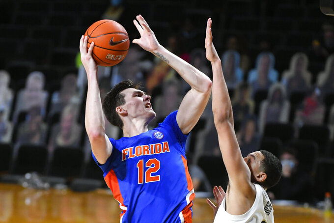 Florida forward Colin Castleton (12) shoots as Vanderbilt forward Dylan Disu defends during the second half of an NCAA college basketball game Wednesday, Dec. 30, 2020, in Nashville, Tenn. Florida won 91-72. (AP Photo/John Amis)