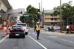 CORRECTS BYLINE TO MARCO GARCIA INSTEAD OF CALEB JONES - Police redirect traffic from the Makalapa Gate entrance to Joint Base Pearl Harbor-Hickam, Wednesday, Dec. 4, 2019, in Honolulu, following a shooting at Pearl Harbor naval shipyard. (AP Photo/Marco Garcia)