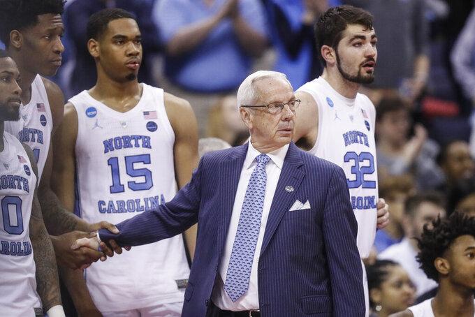North Carolina coach Roy Williams congratulates his players in the final moments of the second half during a second-round men's college basketball game against Washington in the NCAA Tournament, Sunday, March 24, 2019, in Columbus, Ohio. (AP Photo/John Minchillo)