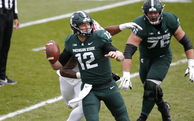 Michigan State quarterback Rocky Lombardi (12) is sacked by Ohio State's Tyreke Smith, rear, during the first half of an NCAA college football game, Saturday, Dec. 5, 2020, in East Lansing, Mich. (AP Photo/Al Goldis)