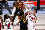 Los Angeles Lakers forward LeBron James scores between Miami Heat forward Jae Crowder, left, and guard Tyler Herro during the second half in Game 5 of basketball's NBA Finals Friday, Oct. 9, 2020, in Lake Buena Vista, Fla. (AP Photo/John Raoux)