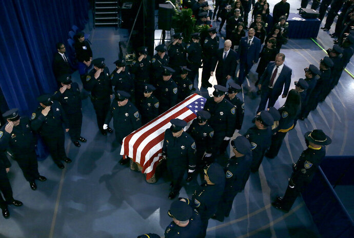 Davis Police officers salute the flag draped coffin of Davis Police Officer Natalie Corona after funeral services for Corona at the University of California, Davis, Friday, Jan. 18, 2019, in Davis, Calif. Corona was was shot and killed Jan. 10, responding to scene of a three-car crash in Davis. Police say gunman Kevin Douglas Limbaugh, 48, not involved in the crash, rode up on a bicycle and without warning, opened fire on Corona. (AP Photo/Rich Pedroncelli, Pool)