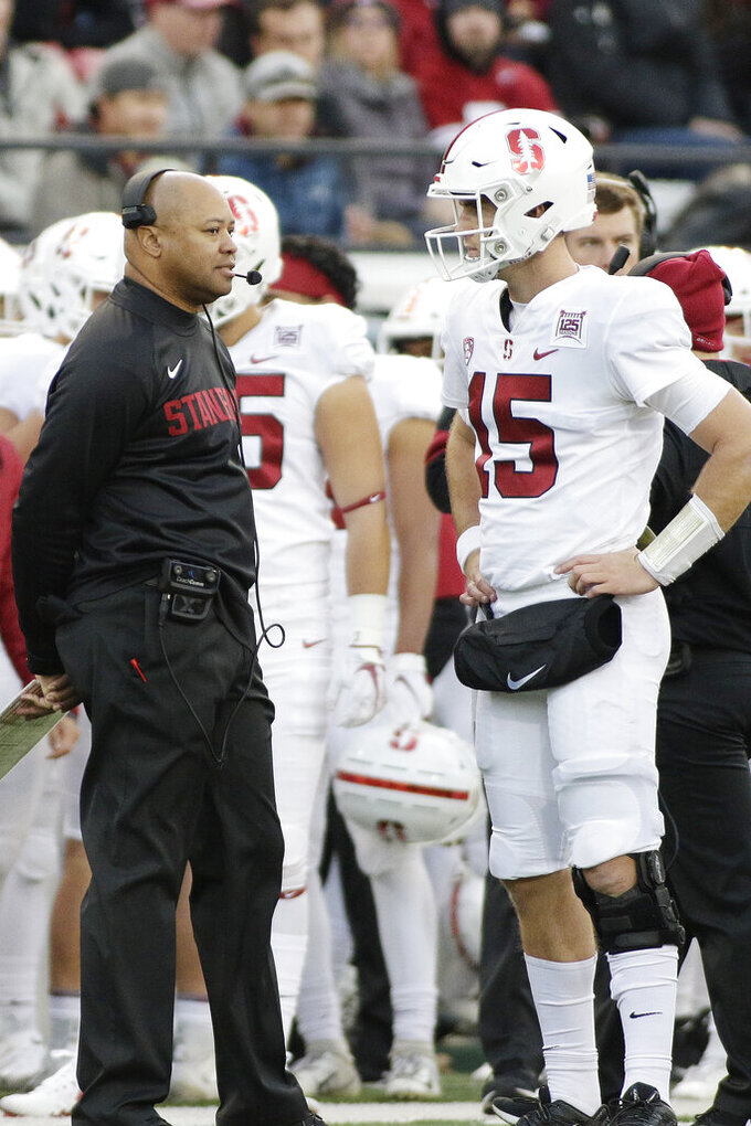 Stanford head coach David Shaw, left, speaks with quarterback Davis Mills (15) during the second half of an NCAA college football game against Washington State in Pullman, Wash., Saturday, Nov. 16, 2019. Washington State won 49-22. (AP Photo/Young Kwak)