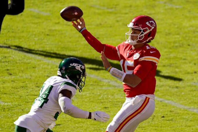 New York Jets cornerback Brian Poole (34) pressures as Kansas City Chiefs quarterback Patrick Mahomes (15) throws a pass in the second half of an NFL football game on Sunday, Nov. 1, 2020, in Kansas City, Mo. (AP Photo/Charlie Riedel)