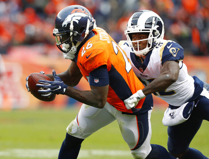 FILE - In this Oct. 14, 2018, file photo, Denver Broncos strong safety Darian Stewart (26) intercepts a pass intended for Los Angeles Rams running back John Kelly during the second half of an NFL football game in Denver. The former safety announced his retirement from the NFL on Thursday, Dec. 10, 2020, saying he's turned his focus to his foundation in Charlotte, North Carolina, and wants to give back to his alma mater, the University of South Carolina. (AP Photo/Joe Mahoney, File)