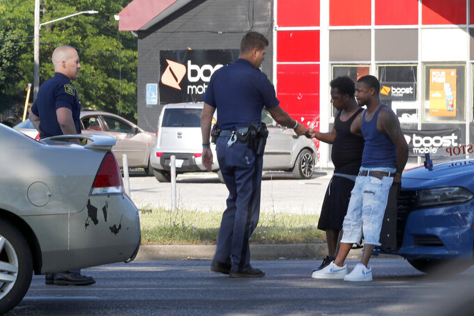 Michigan State Troopers talk with two Black men Monday, June 29, 2020, during a stop on the impoverished east side of Saginaw, Mich. Black residents have largely long been relegated to the east side of the city, where blighted and abandoned buildings line streets – remnants of the Great Recession from a decade ago. (AP Photo/Charles Rex Arbogast)