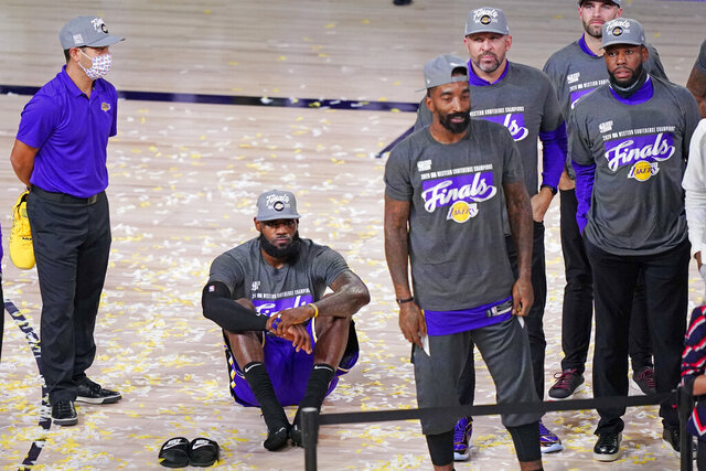 Los Angeles Lakers' LeBron James sits on the floor as he waits for the trophy ceremony to start after the Lakers beat the Denver Nuggets in an NBA conference final playoff basketball game Saturday, Sept. 26, 2020, in Lake Buena Vista, Fla. The Lakers won 117-107 to win the series 4-1. (AP Photo/Mark J. Terrill)