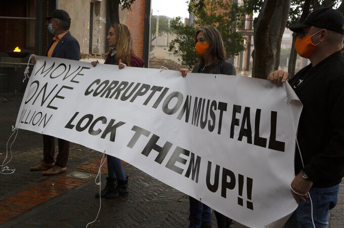 Protesters against former South African President Jacob Zuma demonstrate outside the Constitutional Court in Johannesburg, Thursday, March 25, 2021.Lawyers for a commission investigating corruption in South Africa have asked the country's highest court to jail Zuma for failing to cooperate with its probe against state capture. (AP Photo/Denis Farrell).
