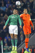 Northern Ireland's Josh Magennis jumps for the ball with Netherlands' Virgil Van Dijk, right, during the Euro 2020 group C qualifying soccer match between Northern Ireland and the Netherlands at Windsor Park, Belfast, Northern Ireland, Saturday, Nov. 16, 2019. (AP Photo/Peter Morrison)