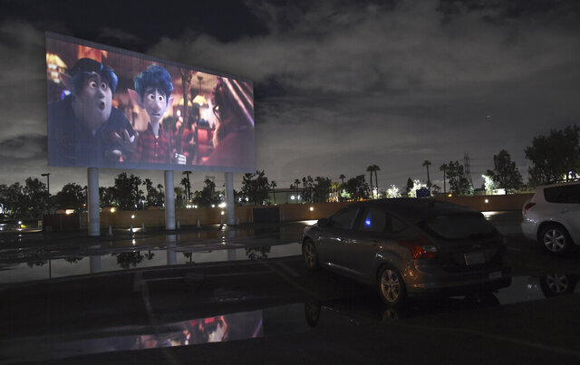 FILE - In this March 19, 2020 file photo, viewers in a parked car watch the animated film