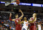 Virginia's Mamadi Diakite (25) after shooting looks for the rebound while defended by Oklahoma's Matt Freeman (5) and Brady Manek (35) during the second half of a second round men's college basketball game in the NCAA Tournament in Columbia, S.C. Sunday, March 24, 2019. (AP Photo/Richard Shiro)