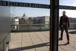 In this Friday, Dec. 20, 2019, photo, a man walks onto the terrace with the Capitol in the background at the Newseum in Washington. The Newseum will close the Pennsylvania Avenue location on Dec. 31, 2019. It attracted millions of visitors but lacked a solid financial plan to stay afloat. The mission of the Newseum is to increase public understanding of the importance of a free press and the First Amendment. (AP Photo/Jacquelyn Martin)