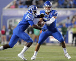 Memphis quarterback Brady White, right, shuffles the ball to running back Kylan Watkins during an NCAA college football game against Tulane on Saturday, Oct. 19, 2019, in Memphis, Tenn. (Jim Weber/Daily Memphian via AP)