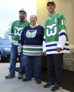 Hartford Whalers Booster Club members, from left, Scott St. Laurent, Joanne Coressa and Dan Narvesen pose outside a Manchester, Conn., restaurant on Thursday, May 9, 2019, where they gathered to watch Game 1 of the NHL Eastern Conference playoff series between the Carolina Hurricanes and the Boston Bruins. (AP Photo/Pat Eaton-Robb)