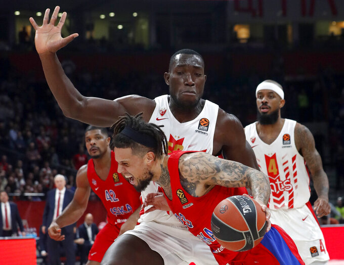 In this photo taken Friday, Feb. 21, 2020, CSKA Moscow's Daniel Hackett, front, drives to the basket as Red Star's Michael Ojo blocks him during their Euroleague basketball match in Belgrade, Serbia. Former Florida State center Michael Ojo has died after collapsing during training in Serbia. Serbian Media and his former teammates say the 27-year-old Nigerian-born basketball player was on Friday taken to a hospital in the Serbian capital, but doctors failed to reanimate him. (AP Photo/Darko Vojinovic)