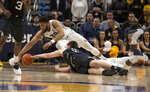 Marquette's Ed Marrow, left, dives for the loose ball against Butler's Nate Fowler, right, during the first half of an NCAA college basketball game Wednesday, Feb. 20, 2019, in Milwaukee. (AP Photo/Darren Hauck)