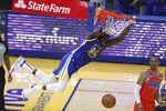 Golden State Warriors' Draymond Green hangs from the rim after scoring against Oklahoma City Thunder's Darius Bazley during the first half of an NBA basketball game in San Francisco, Saturday, May 8, 2021. (AP Photo/Jed Jacobsohn)