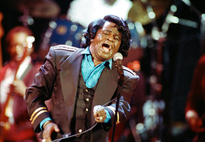 """FILE - In this Monday, June 10, 1991 file photo, James Brown sings """"Living in America"""" during his three-hour concert at the Wiltern Theater in Los Angeles. The family of entertainer James Brown has reached a settlement ending a 15-year battle over late singer's estate. David Black, an attorney representing Brown's estate, confirmed to The Associated Press on Friday, July 23, 2021 that the agreement was reached July 9. (AP Photo/Kevork Djansezian, File)"""
