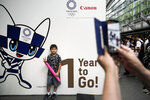 A boy pauses for photos during a One Year to Go ceremony held at Tokyo International Forum to mark one year until the opening of the Tokyo 2020 Olympics, Wednesday, July 24, 2019, in Tokyo. Fans, sponsors and politicians celebrated the day around the Japanese capital, displaying placards and clocks showing 365 days to go until the opening ceremony on July 24, 2020. (AP Photo/Jae C. Hong)