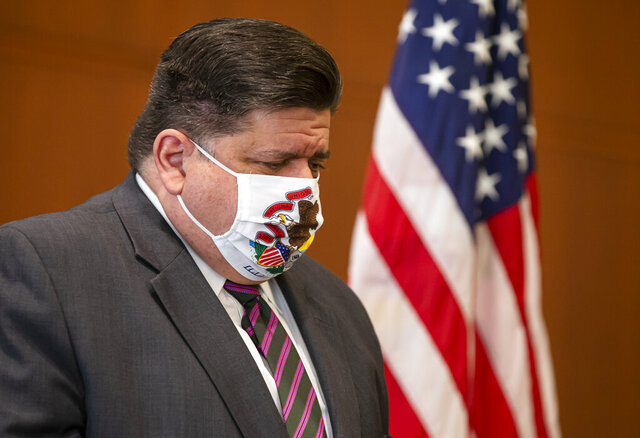 FILE - In this Sept. 21, 2020 file photo, Illinois Governor JB Pritzker lowers his head as Illinois Department of Public Health Director Dr. Ngozi Ezike announces seven additional deaths due to COVID-19 during a press conference in Springfield, Ill. While battling a recalcitrant coronavirus pandemic, Gov. J.B. Pritzker on Wednesday, Oct. 21, 2020, started laying plans for distributing a safe and effective vaccine. (Justin L. Fowler/The State Journal-Register via AP)
