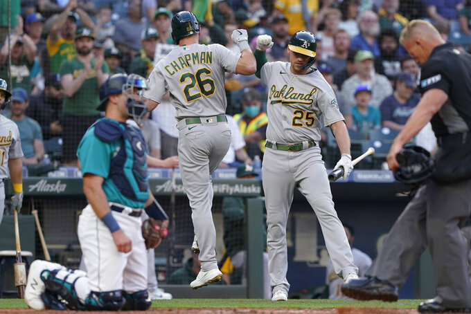Oakland Athletics' Matt Chapman (26) greets Stephen Piscotty (25) after Chapman hit a solo home run during the third inning of the team's baseball game against the Seattle Mariners, Friday, July 23, 2021, in Seattle. (AP Photo/Ted S. Warren)