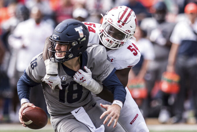 FILE - In this Oct. 19, 2019, file photo, Illinois quarterback Brandon Peters (18) is sacked by Wisconsin's Chris Orr (54) in the second half of an NCAA college football game, in Champaign, Ill. Championship weekend crowns the winner of 10 FBS conferences and matches up some big-time players. Wisconsin and Ohio State will meet for the Big Ten Championship. (AP Photo/Holly Hart, File)
