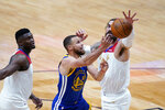 Golden State Warriors guard Stephen Curry (30) goes to the basket against New Orleans Pelicans center Steven Adams and forward Zion Williamson, left, in the first half of an NBA basketball game in New Orleans, Tuesday, May 4, 2021. (AP Photo/Gerald Herbert)