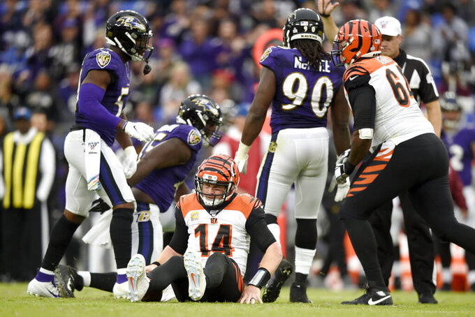 Cincinnati Bengals quarterback Andy Dalton (14) is slow to get up after being sacked by a host of Baltimore Ravens linemen during the second half of a NFL football game Sunday, Oct. 13, 2019, in Baltimore. The Ravens won 23-17. (AP Photo/Gail Burton)