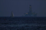 An offshore drilling rig is seen in the waters off Cyprus' coastal city of Limassol as a sailboat sails in the foreground on Sunday, July 5, 2020. Cyprus has in recent years been a resupply stop for rigs drilling in the eastern Mediterranean, including waters were the Cypriot government has licensed international energy companies to search of hydrocarbons. (AP Photo/Petros Karadjias)