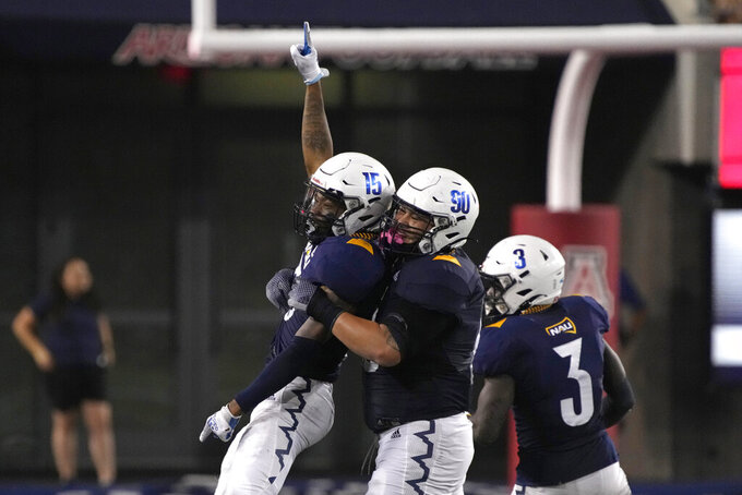 Northern Arizona defensive back Devontae Ingram (15) celebrates with Mark Ho Ching (90) after intercepting a pass against Arizona during the second half of an NCAA college football game, Saturday, Sept. 18, 2021, in Tucson, Ariz. (AP Photo/Rick Scuteri)
