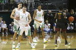 Oregon's Chris Duarte, left, Payton Pritchard and Chandler Lawson celebrate as Southern California's Jonah Mathews heads to the bench during overtime of an NCAA basketball game in Eugene, Ore., Thursday, Jan. 23, 2020. (AP Photo/Chris Pietsch)