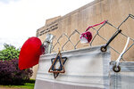Mementos hang from the fence surrounding the Tree of Life synagogue, which housed three congregations, New Light, Dor Hadash and Tree of Life, Monday, May 3, 2021, in the Squirrel Hill neighborhood of Pittsburgh. Tree of Life officials last week announced Daniel Libeskind as lead architect for the reconstruction of their synagogue, where in October 2018 a gunman killed 11 worshipers. (Alexandra Wimley/Pittsburgh Post-Gazette via AP)