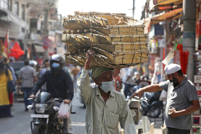 An Indian villager wearing a face mask as a precaution against the coronavirus sells his ware at market in Jammu, India, Friday, Oct. 9, 2020. India is the world's second most coronavirus affected country after the United States. (AP Photo/Channi Anand)