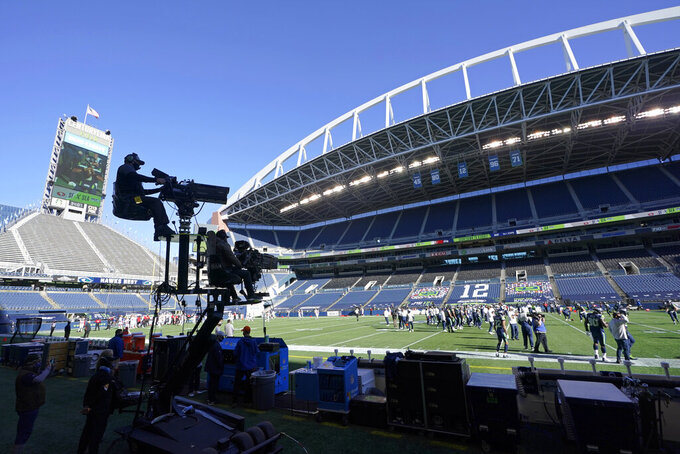 Two TV cameras mounted on a moving cart stand ready to capture action before an NFL football game between the Seattle Seahawks and the San Francisco 49ers, Sunday, Nov. 1, 2020, in Seattle. No fans were allowed in CenturyLink Field for the game due to the COVID-19 pandemic, leaving the TV broadcast as the only way for fans to experience the game. (AP Photo/Elaine Thompson)