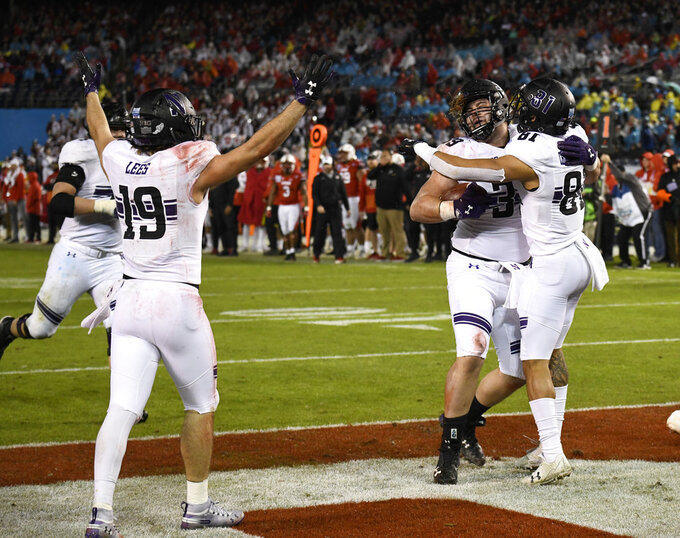 Northwestern offensive lineman Trey Klock (39), center, is congratulated by wide receiver Ramaud Chiaokhiao-Bowman (81) after scoring a touchdown during the second half of the Holiday Bowl NCAA college football game against Utah, Monday, Dec. 31, 2018, in San Diego. (AP Photo/Denis Poroy)