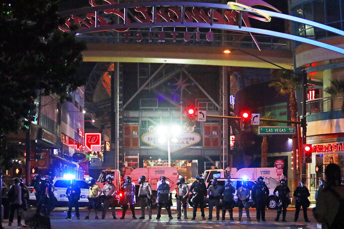 Police stand in formation at the entrance to Fremont Street Experience Monday, June 1, 2020, in downtown Las Vegas. Police were present for a community protest over the death of George Floyd, a Minneapolis man who died in police custody on Memorial Day. (AP Photo/Ronda Churchill)
