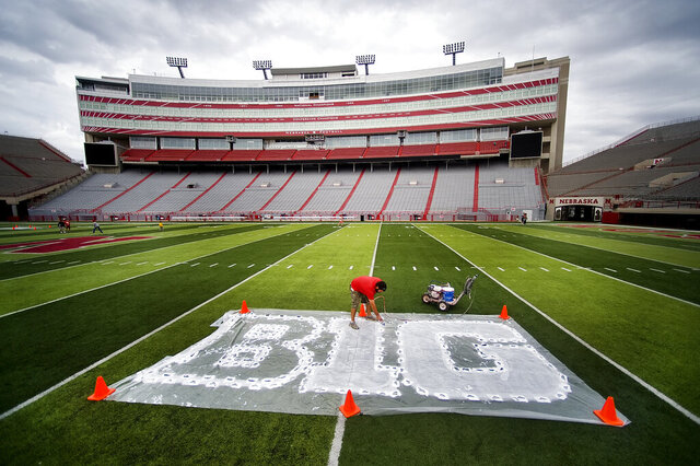 FILE - In this Thursday, Oct. 6, 2011 file photo, Turf manager Jared Hertzel touches up the newly-painted Big Ten conference logo on the football field at Memorial Stadium in Lincoln, Neb. The Big Ten Conference announced Thursday, July 9, 2020 it will not play nonconference games in football or several other sports this fall because of the coronavirus pandemic. (Jacob Hannah/Lincoln Journal Star via AP)