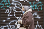 A woman wearing a face mask to protect against coronavirus walks past a closed shop in Ivano-Frankivsk, Western Ukraine, Friday, Jan. 8, 2021. Ukraine imposed a wide-ranging lockdown beginning Friday, closing schools and entertainment venues and restaurant table service through Jan. 25. (AP Photo/Evgeniy Maloletka)