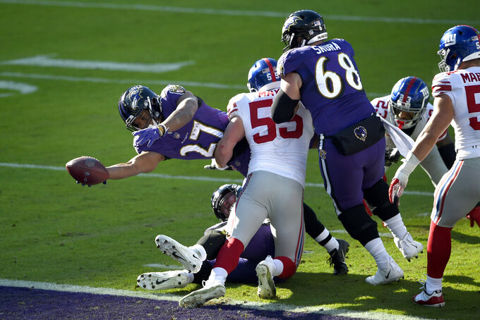 Baltimore Ravens running back J.K. Dobbins (27) dives across the goal line while scoring a touchdown on a run as New York Giants outside linebacker David Mayo (55) tries to stop him during the first half of an NFL football game, Sunday, Dec. 27, 2020, in Baltimore. (AP Photo/Gail Burton)