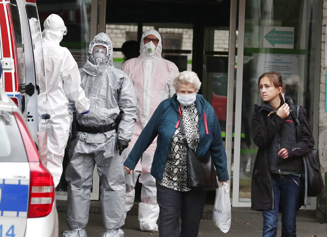 Women with and without anti-coronavirus masks pass by an ambulance team wearing anti-COVID-19 outfits at a hospital in Warsaw, Poland, Thursday, Oct. 8, 2020.  Poland's government has announced the entire country a yellow zone after the number of new registered case of coronavirus infection spiked to almost 4,300 on Thursday. The yellow zone rules take effect Saturday and will require Poles to wear masks in all public spaces, also in the open air. (AP Photo/Czarek Sokolowski)