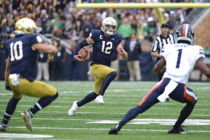 Notre Dame quarterback Ian Book (12) runs with the ball in front of Virginia cornerback Nick Grant (1) in the first half of an NCAA college football game in South Bend, Ind., Saturday, Sept. 28, 2019. (AP Photo/AJ Mast)