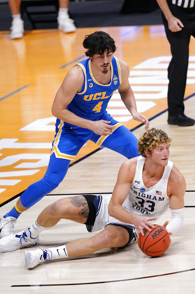 BYU forward Caleb Lohner (33) looks for help as UCLA guard Jaime Jaquez Jr. (4) closes in during the first half of a first-round game in the NCAA college basketball tournament at Hinkle Fieldhouse in Indianapolis, Saturday, March 20, 2021. (AP Photo/AJ Mast)